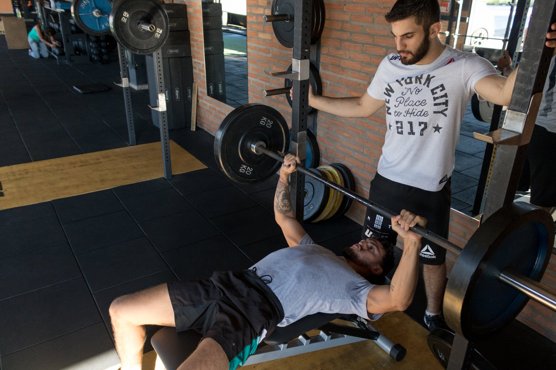 man lying while doing barbell- BENCH PRESS EXERCISE